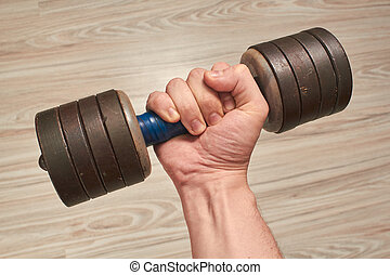 male hand holds a dumbbell at home in quarantine on a background of light wooden parquet