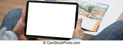 Male hand holds tablet in home setting while - Male hand...