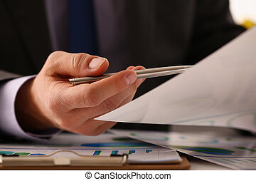 Male hand in suit hold siver pen in office