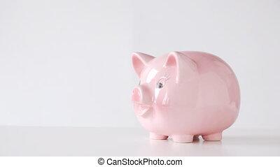 male hand inserting euro money into piggy bank