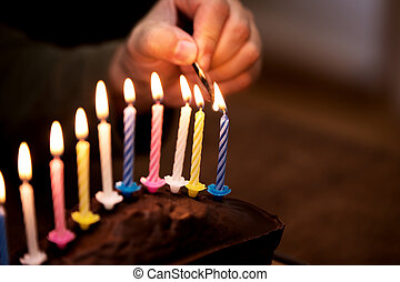 male hand is lightning up some colorful candles on a marble...