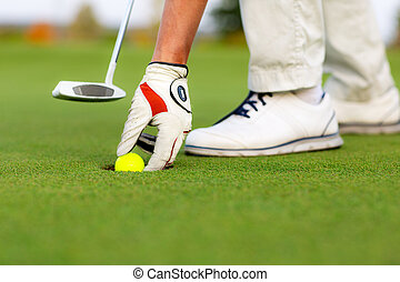 Male hand is putting out a ball from golf hole