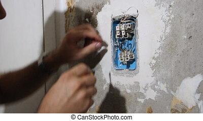 Male hand is repairing socket. HD