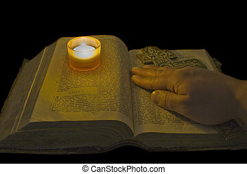 Male hand lies on ancient bible with a big christian cross in the light of a candle over black background