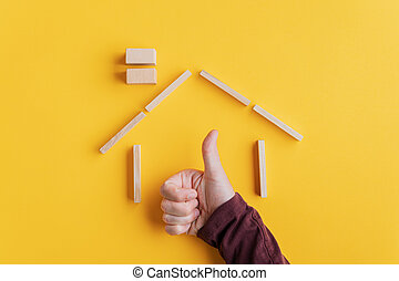 Male hand making a thumbs up gesture holding his hand inside a house made of wooden pegs