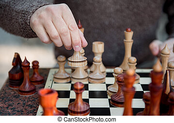 Male hand moving figurine on chessboard
