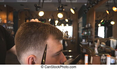 Male hand of hairdresser combing hair of young man in...