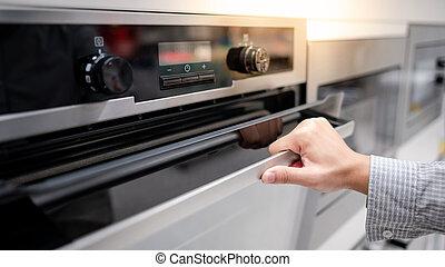 Male hand opening oven door