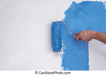 Male hand painting wall in blue with paint roller.