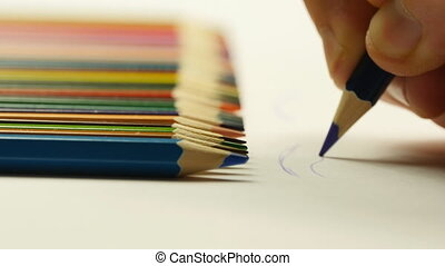Male hand painting with colored pencils and putting pencil