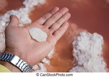 Male hand piece salt on pink water - extraction sea salt