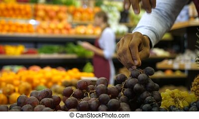 Male hand placing fresh grape in grocery store - Close-up of...