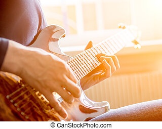 Male hand playing on acoustic guitar. Close-up. Sunflare