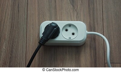 Male hand plugging black power plug into white multiple...