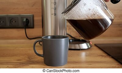 Male hand pours coffee into a mug on the background of the coffee maker.
