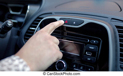 Male hand pressing emergency warning button on car console