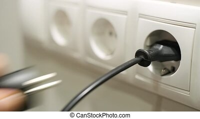 Male hand pulling electrical plugs from sockets, concept of...