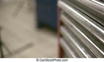 Male hand pushes one of the metal tool boxes and takes the...