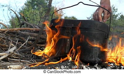 Male hand puts brushwood under the cauldron on a fire in...