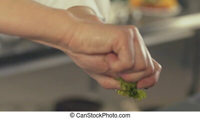 Male hand putting greens into pan, close up