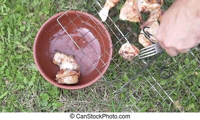 Male hand removing barbecue fork from the grid