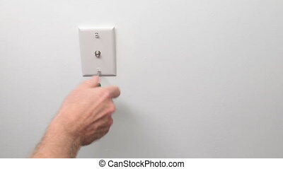 Male Hand Screwing in a Cable Outlet in a White Wall