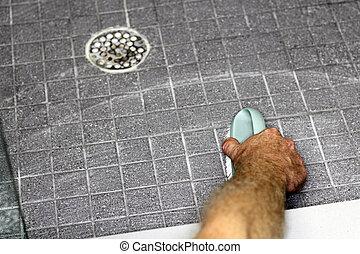 Male Hand Scrubbing Shower Floor