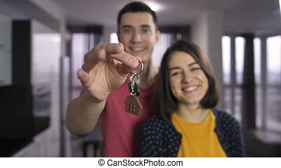 Male hand shaking keys to new house indoors