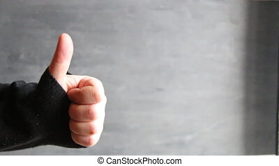 male hand showing thumbs up sign against gray background