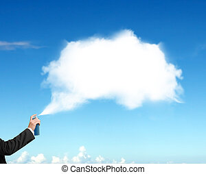 Male hand spraying white cloud paint on blue sky