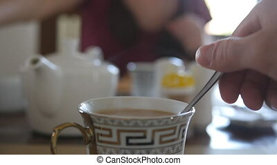 Male hand stirring sugar or milk in a cup of hot coffee or...