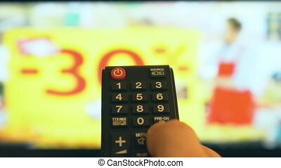 Male hand switching channels on TV with remote control.