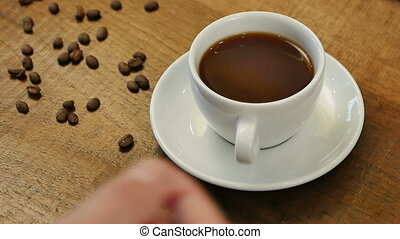 Male hand takes hot coffee to drink. Close up. Slow motion....