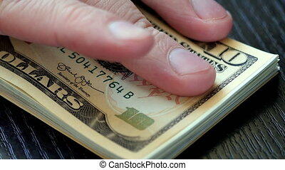 Male hand taking a pile of dollar bills from the black...