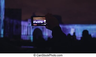 Male hand taking video to 3D mapping light show on a mobile...