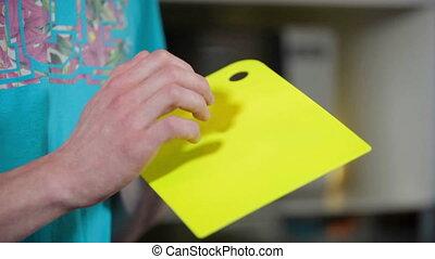 Male hand terting on yellow cutting board. Music kitchen