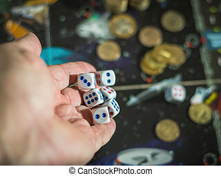 Male hand throwing dice on the playing field with money. The concept of gambling.
