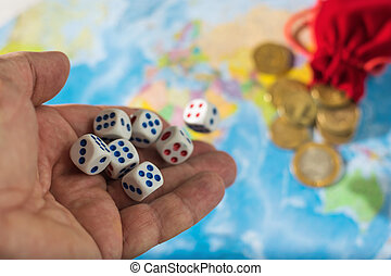 Male hand throwing dice on the table with a world map and money. The concept of ownership of the world. World order.