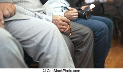 Male hand touches the rosary at the muslim conference, close...