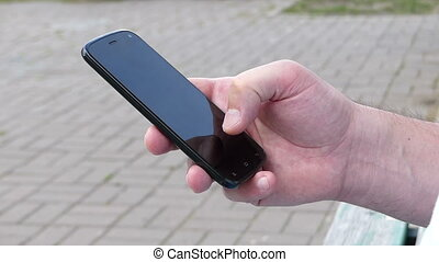 Male hand touches the screen of a mobile telephone on a street