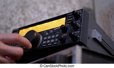 Male Hand Tunes Radio Communication Transceiver at Stationary Radio Station. Manual tuning of signal at different frequencies. Control panel with black buttons, orange dial. Amateur Radio station. 4K
