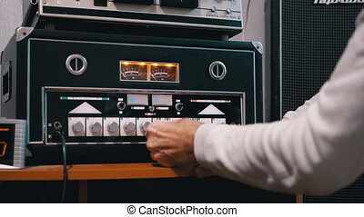 Male hand tunes sound on old stereo power amplifier. Indicator Arrows, Illuminated Decibel Meters. Tumblers, knobs, buttons, dial. Dual analogue scale audio level meter. Quality sound disco. Close. 4K