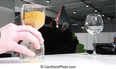 Male hand turns the hourglass during business conference