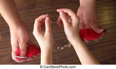 Male hand wear on girl handcuffs for sex games