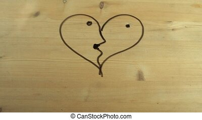 Male hand whipes out heart shape turned into kissing couple on wooden surface