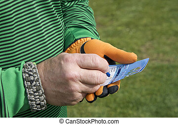 Male hand with golf score card keeping score writing down score