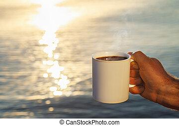 male hand with mug of coffee