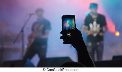 Male Hand with Smartphone Making Video at Live Rock Concert. Slow Motion. Silhouette of Crowd of people at a music festival. Fans near stage are filming a concert. Live broadcast in social networks.
