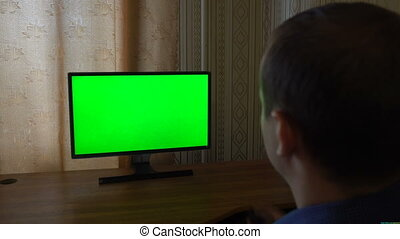 Male Hand With TV Remote Switching Channels On A Green Screen TV Point Of View