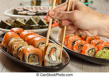 Male hand with two chopsticks holding Uramaki sushi roll